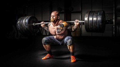 man using weight to squat lift