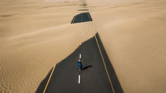 photo of a woman walking down a sand covered road