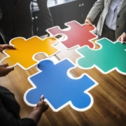 business people putting a puzzle together