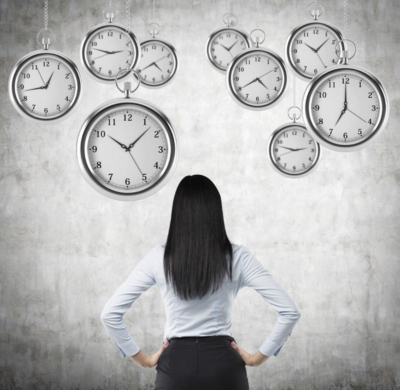photo of a sales manager looking at a wall of clocks