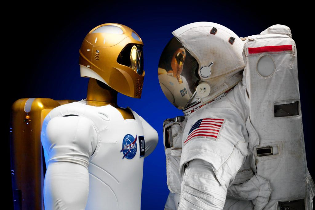 photo of a robot looking at an astronaut