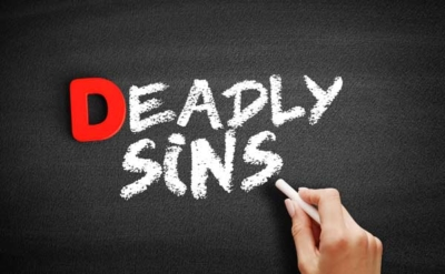 photo of someone writing 'deadly sins' on a chalkboard