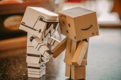 a storm trooper figurine shaking hands with an Amazon figurine